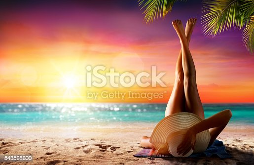 Girl On Sand In Beach At Sunset With Palm Tree
