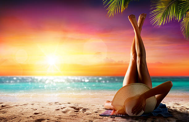 woman in relaxation on tropical beach at sunset - gebruind stockfoto's en -beelden