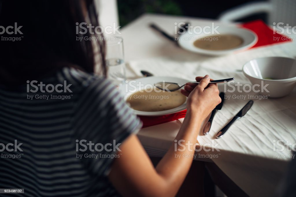 Woman in restaurant eating vegetarian vegan cream soup.Gluten free and diet food.Female eating bone broth based soup.Nutrition and diet.Healthy and light dinner in a hotel. stock photo