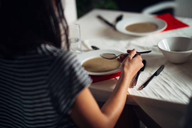 Frau im Restaurant vegetarische vegane Creme Suppe essen. Glutenfrei und Diätkost. Weibliche Essen Knochen Brühe basierte Suppe. Ernährung und Diät. Gesunde und leichte Abendessen in einem Hotel. – Foto