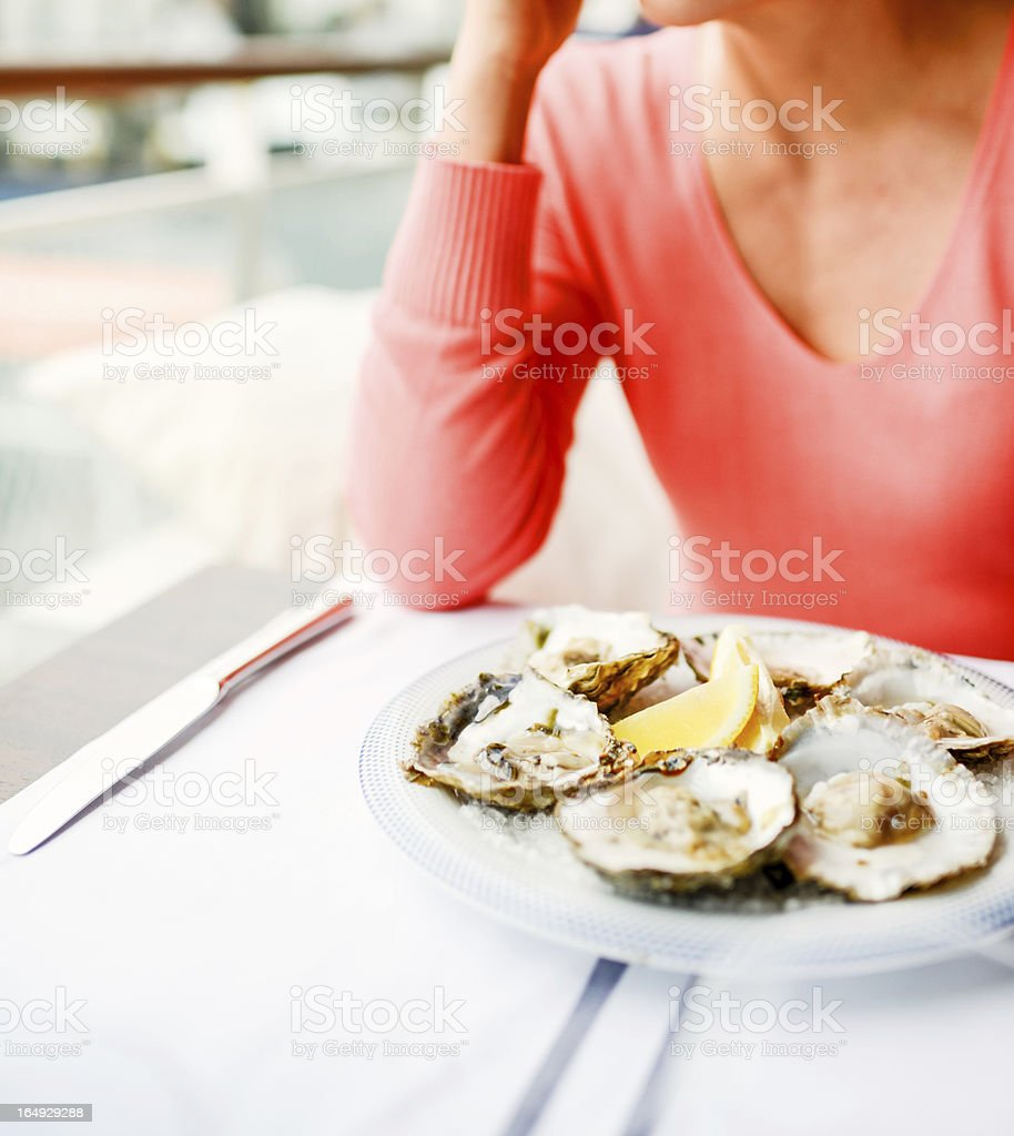 Woman in restaurant with plate of oysters stock photo