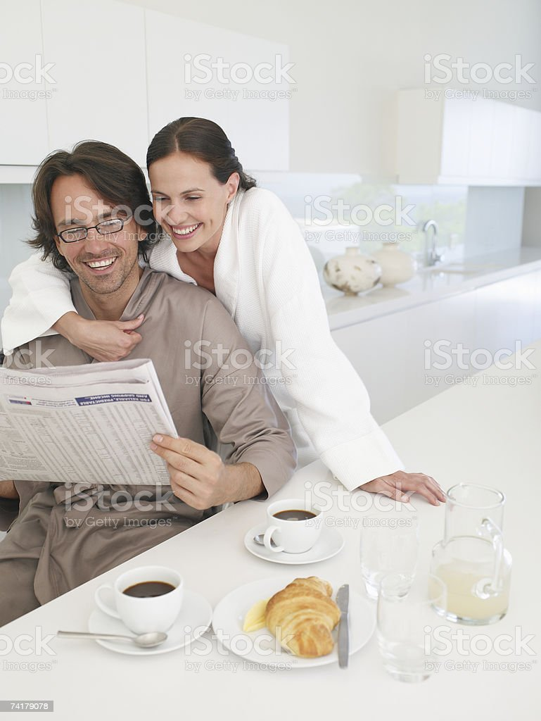 Woman in robe embracing man in robe with newspaper royalty-free stock photo