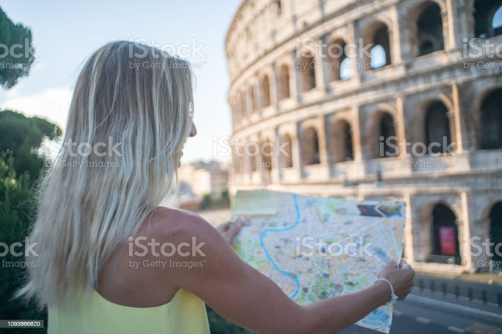 Woman In Rome At The Colosseum Looking At Tourist Map For