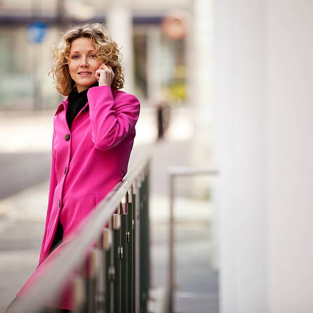 Frau in Rosa Jacke sprechen auf Handy im Freien – Foto