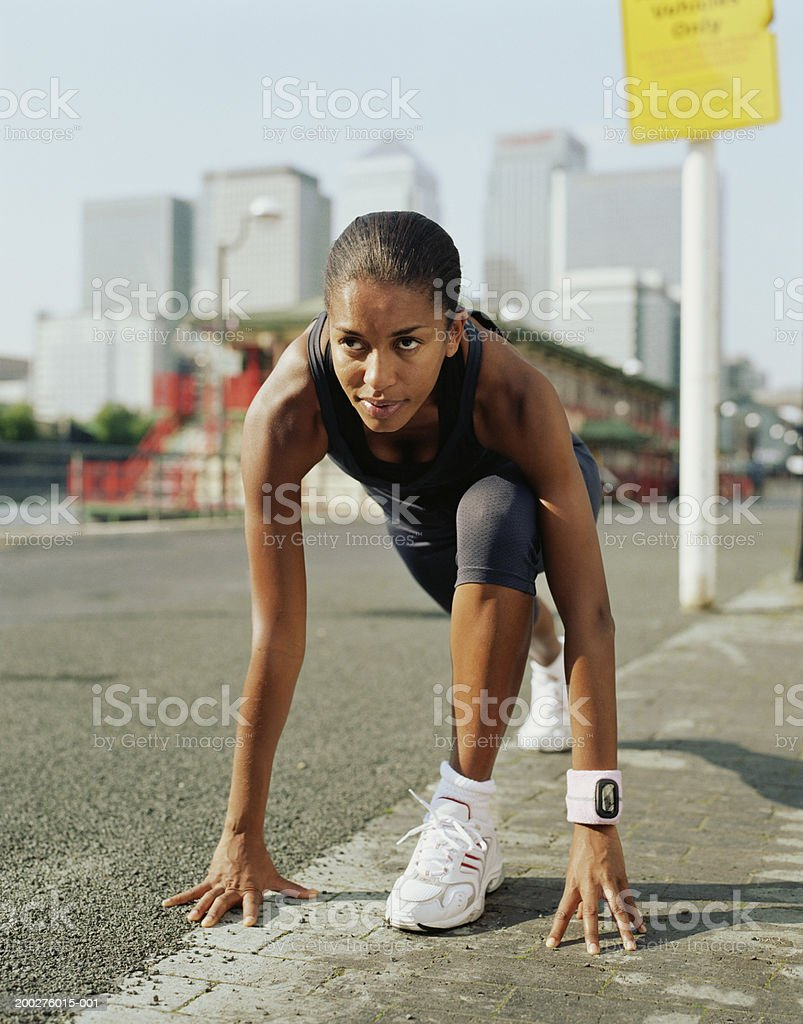Woman in running clothes, in starting position by roadside royalty-free stock photo