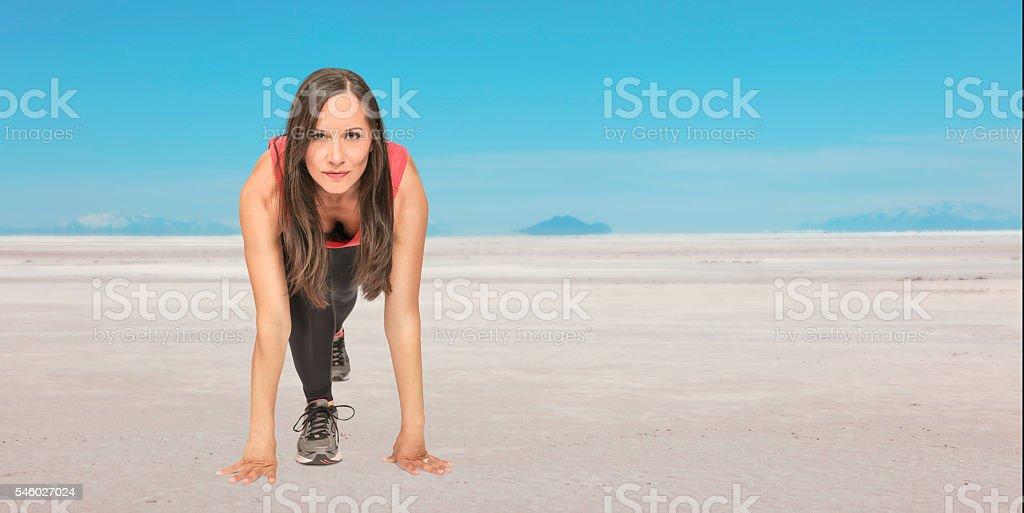 Woman in running set pose salt flats stock photo