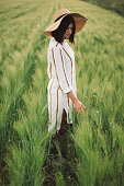 Woman in rustic dress and hat walking in green field of barley. Atmospheric authentic moment. Stylish girl enjoying peaceful evening in countryside. Rural slow life