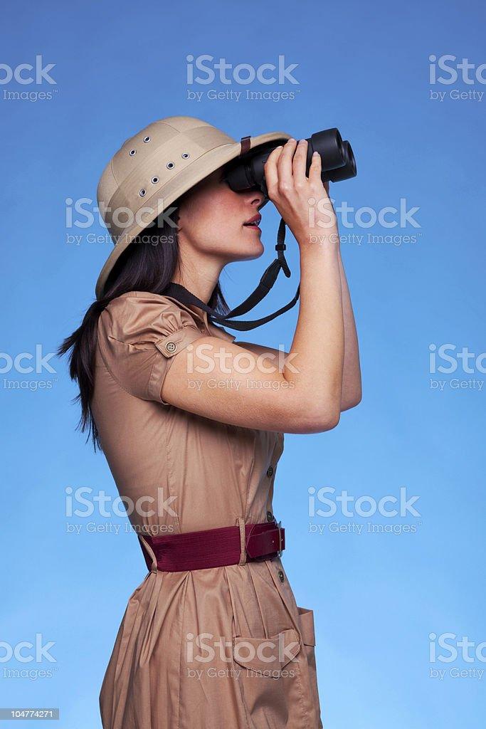 Woman in safari hat looking through binoculars side view stock photo