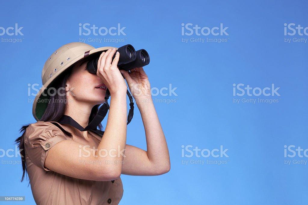 Woman in safari hat searching with binoculars stock photo
