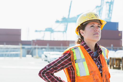 Woman in safety vest, hardhat working at shipping port