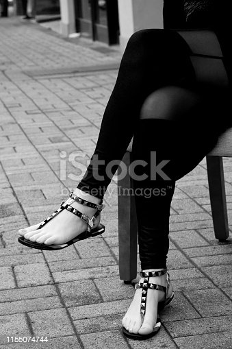 Black and white photograph of female with stylish sandals on sidewalk pavers. Image shot with Canon 5D Mark 4, 24-105mm f/4L IS USM lens.