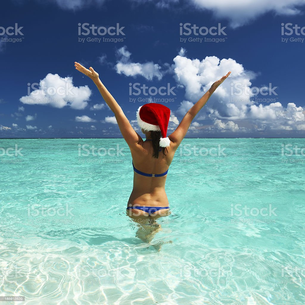 Woman in santa's hat at beach royalty-free stock photo