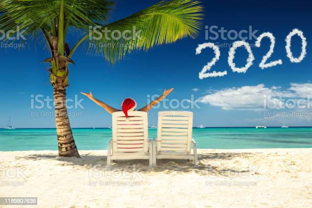 Woman in santa's hat relaxing on tropical beach. Happy new year 2020