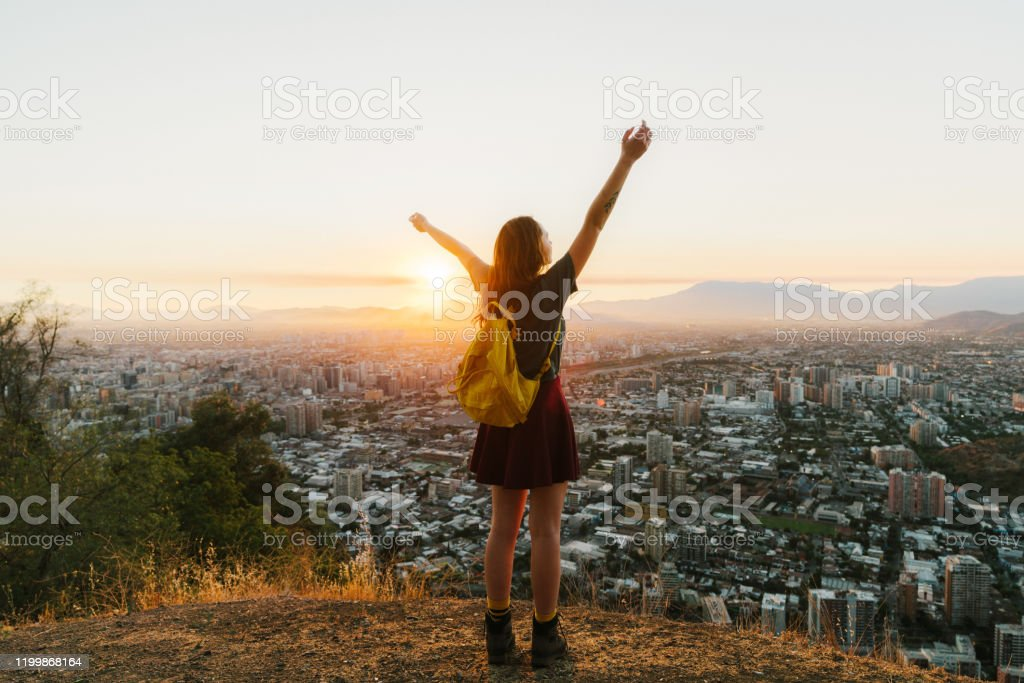 Woman in Santiago at sunset Young Caucasian woman with yellow backpack in Santiago at sunset, Chile Adult Stock Photo