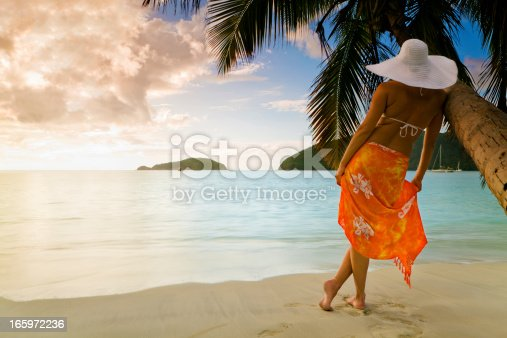 rear view of a woman in orange sarong and white summer hat enjoying the Caribbean view