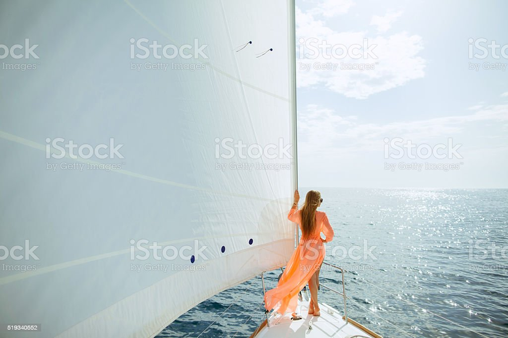 woman in sarong yachting white sails luxury travel stock photo