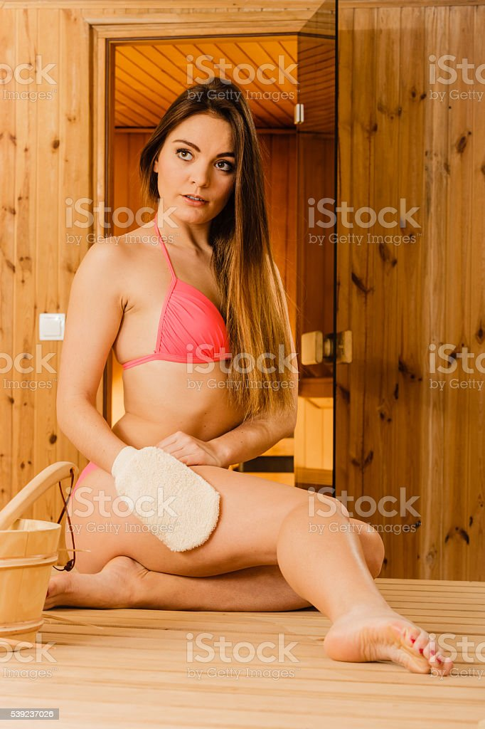 Woman in sauna with exfoliating glove. Skincare. royalty-free stock photo