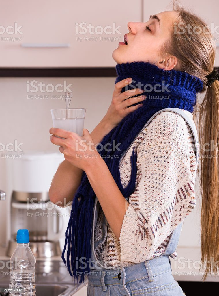 woman in scarf gargling throat with domestic soda stock photo