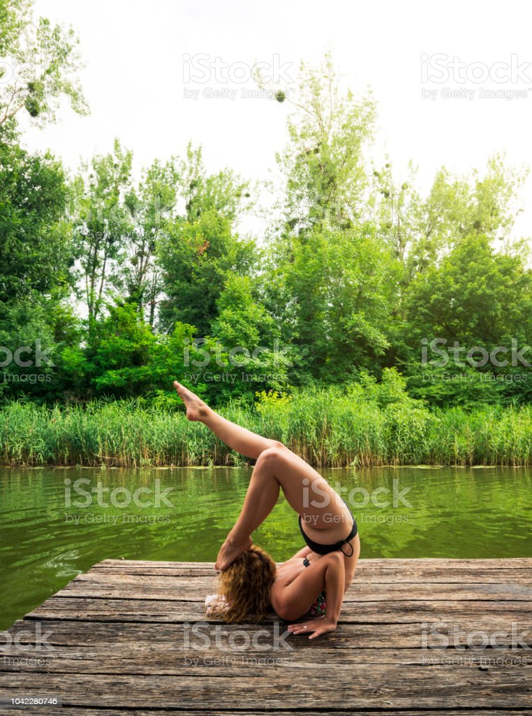 6e5c8b63741de Woman In Scorpion Yoga Pose By The Lake Stock Photo & More Pictures ...