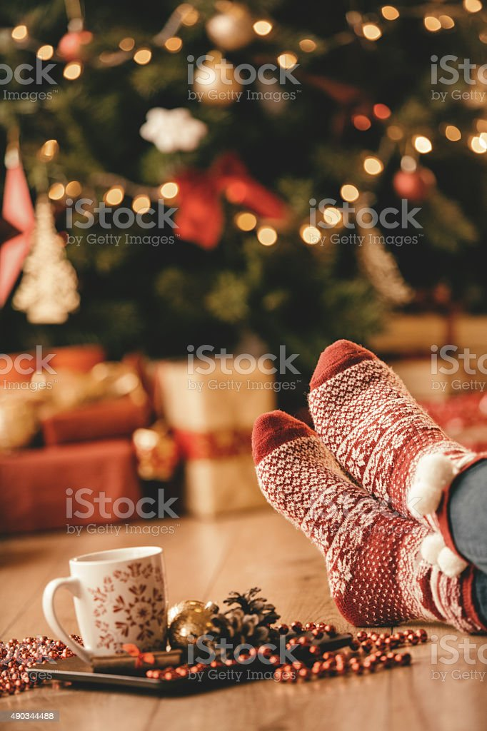 Woman in seasonal socks in front of Christmas tree stock photo