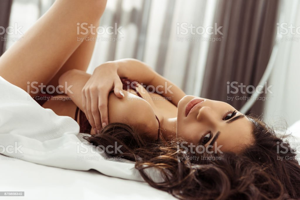 woman in sexy lingerie posing on bed stock photo
