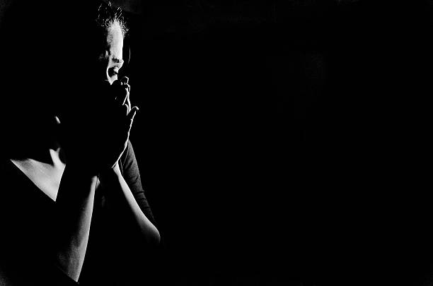 Woman in shadows crying on black Young woman stanging in the dark crying,she is feeling hopless . woman crying stock pictures, royalty-free photos & images