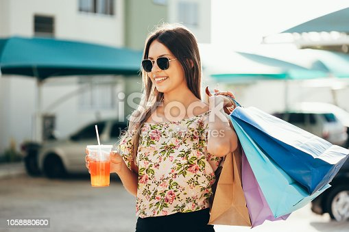 istock Woman in shopping. Happy woman with shopping bags enjoying on the street. Consumerism, shopping, lifestyle concept 1058880600