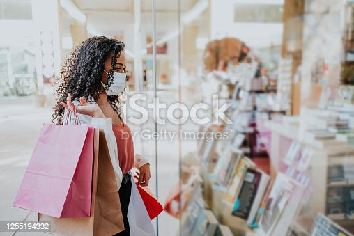 Woman in shopping mall with bags shopping during pandemic and wearing face mask against coronavirus