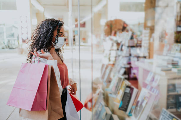 Woman in shopping mall with bags shopping Woman in shopping mall with bags shopping during pandemic and wearing face mask against coronavirus shopping mall stock pictures, royalty-free photos & images
