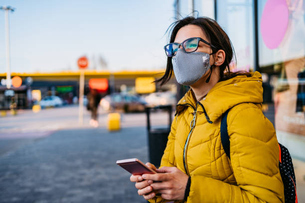 Woman in shopping mall with face mask using phone stock photo