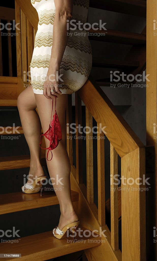 Woman in short skirt dangles red bra walking up stairs royalty-free stock photo