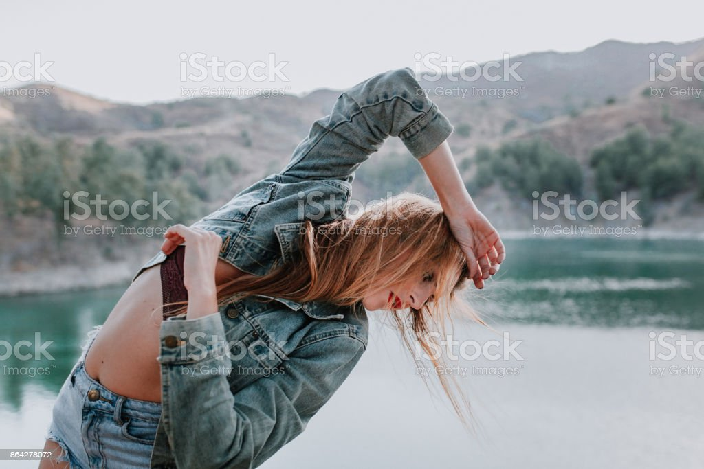Woman in shorts and jacket posing in nature with a lake in the background. royalty-free stock photo