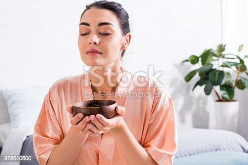 istock woman in silk bathrobe with wooden bowl in hands having tea ceremony in morning at home 978610500