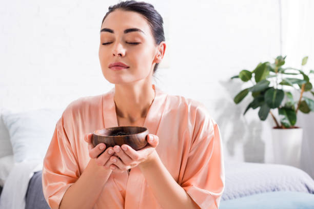 woman in silk bathrobe with wooden bowl in hands having tea ceremony in morning at home woman in silk bathrobe with wooden bowl in hands having tea ceremony in morning at home aromatherapy stock pictures, royalty-free photos & images
