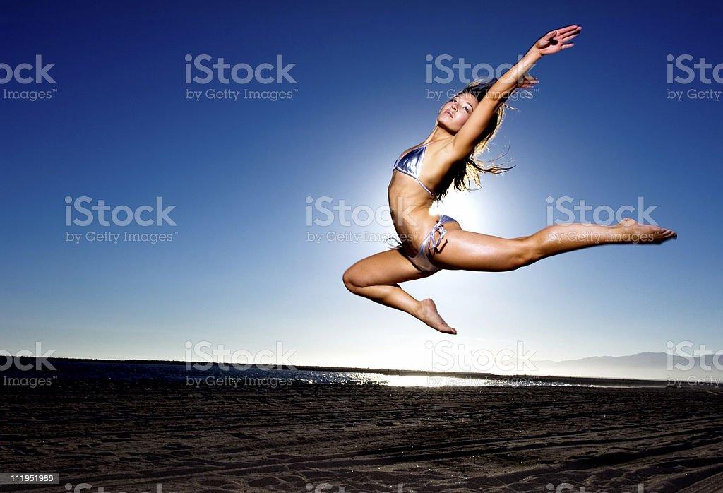 Woman in silver bikini leaping at beach royalty-free stock photo