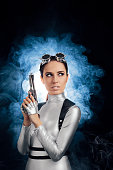 istock Woman in Silver Space Costume Holding Pistol Gun 537334964