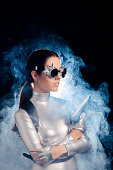 istock Woman in Silver Space Costume Holding Pistol Gun 537334974