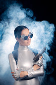 istock Woman in Silver Space Costume Holding Pistol Gun 537334988