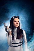 istock Woman in Silver Space Costume Holding Pistol Gun 537335022