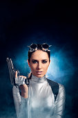 istock Woman in Silver Space Costume Holding Pistol Gun 537335030