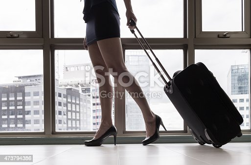 istock Woman in skirt and heels pulling luggage 473794386