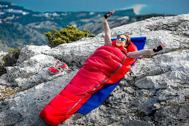 Woman in sleeping bag on the mountain stock photo