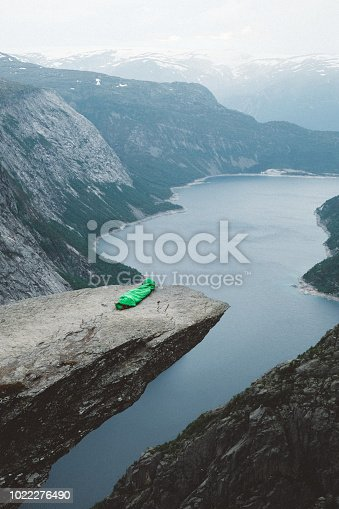Woman sleeping with scenic view of mountains and fjord on Trolltunga in Norway