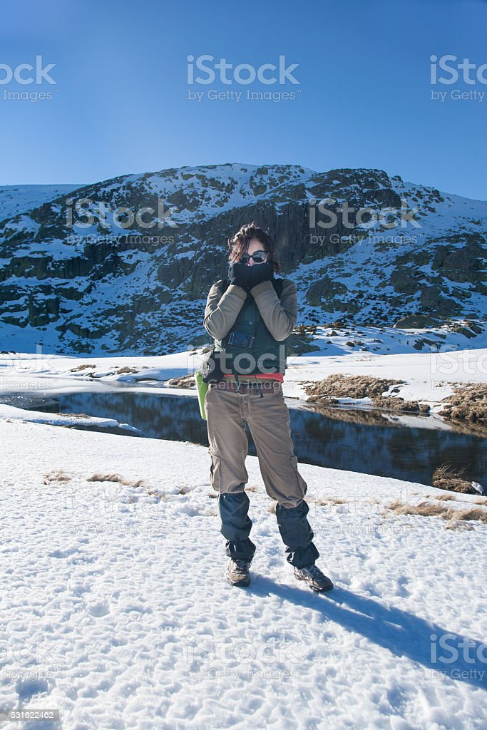 woman in snow looking cold stock photo