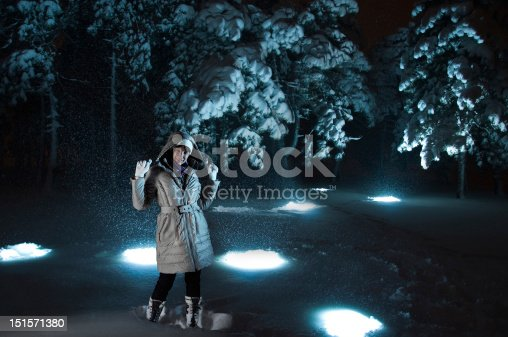 Woman on snowy night with blue flashes in snow