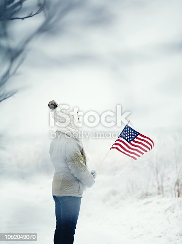 Woman in snowy landscape holding American flag