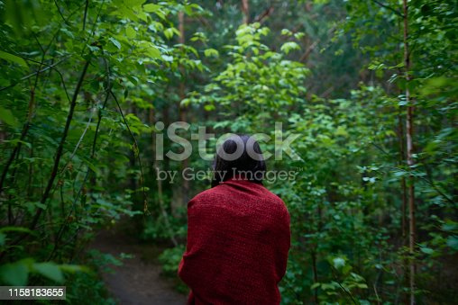 Back view of girl in red cloth walking alone on pathway among green dark trees in woods