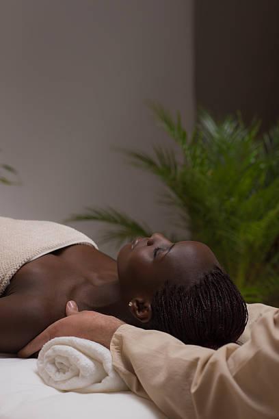 woman in spa environment getting massage - oliven wohnzimmer stock-fotos und bilder
