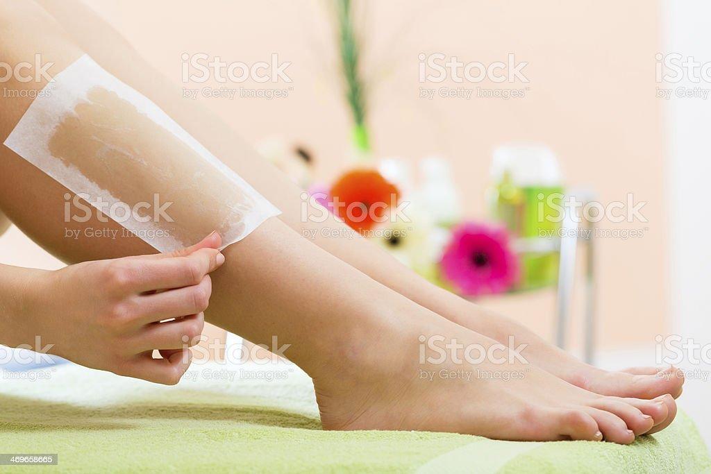 Woman in Spa getting leg waxed stock photo