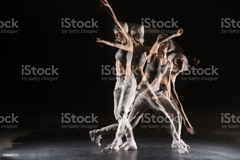 woman in sports clothing dancing on black stock photo